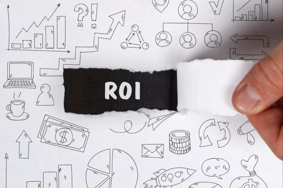 Business, Technology, Internet and network concept. Young businessman shows the word: ROI